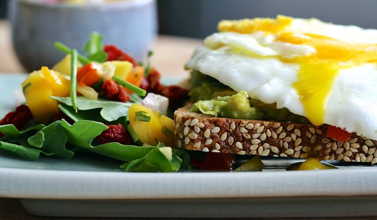 over easy eggs on avocado toast with greens salad